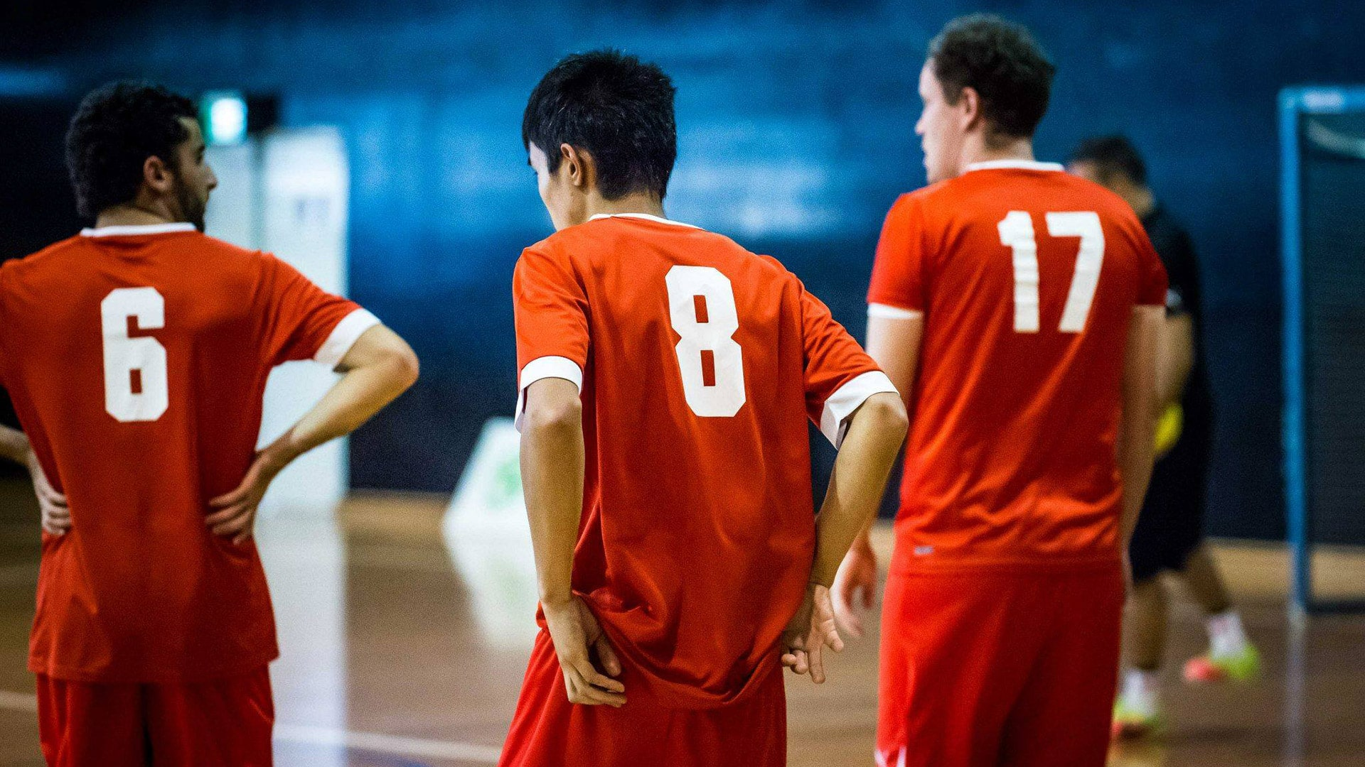 Image shows three male soccer players' backs in red uniforms as the stand on the side of an indoor hall where a game is being played.