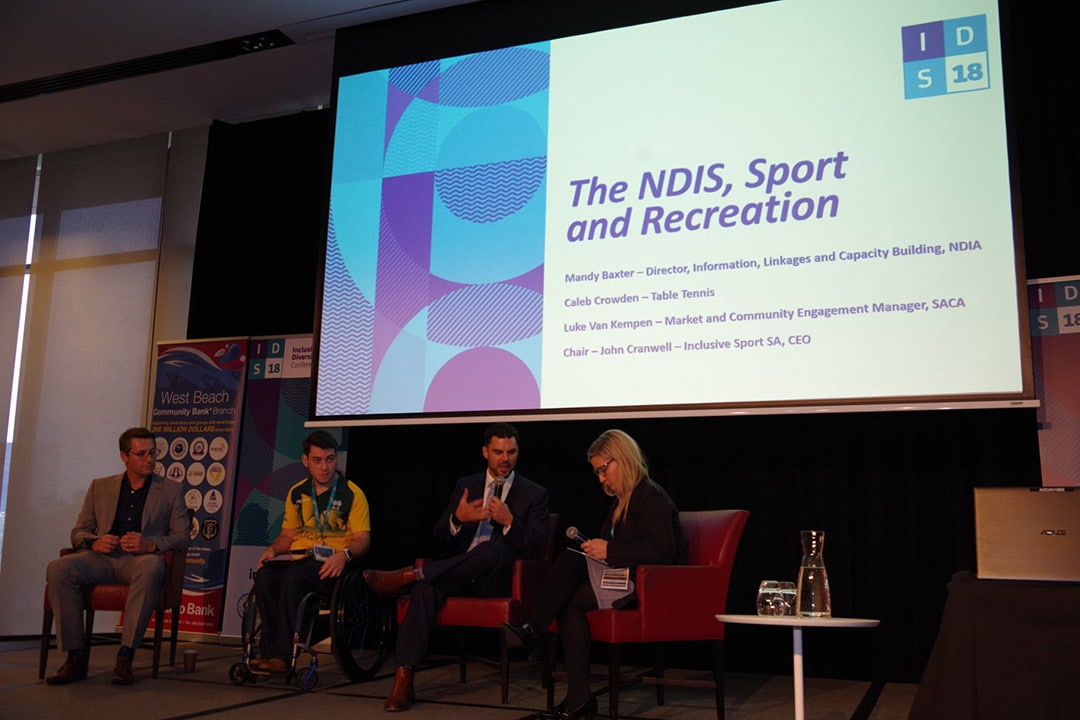a group of four adults sit on a stage in front of a screen that reads The NDIS Sport and Recreation