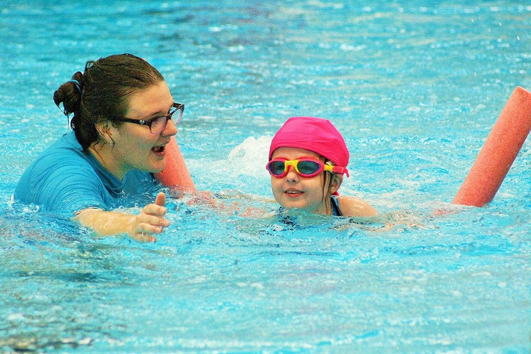 A female swim instructor cheers on a young child swimming in a pool