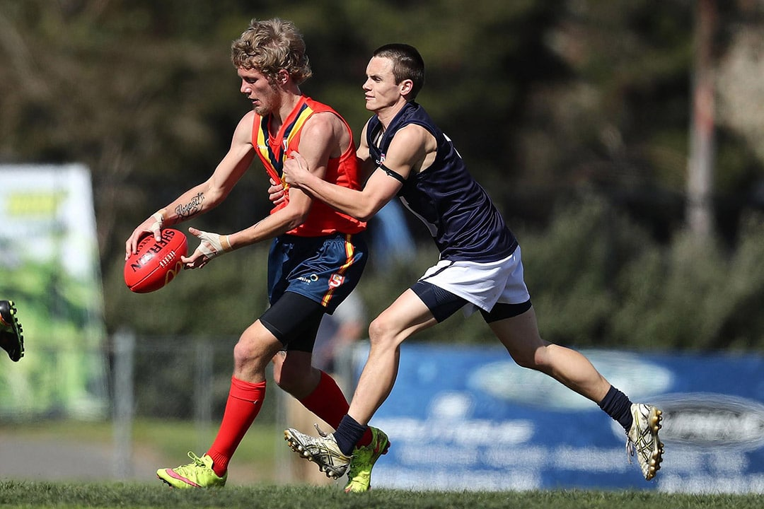 A South Australian football player is holding the football mid game, a Victorian player has begun to tackle him.