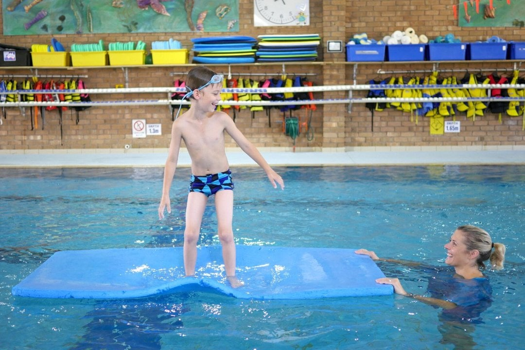 A young boy takes part in an Aquatic session in the pool with a female therapist. He is balancing on a mat and laughing with the woman.