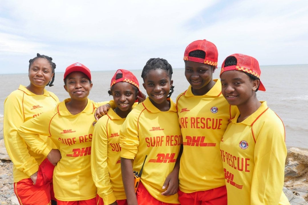 a group of six teenage and young women stand together on the beach wearing lifesaving uniforms