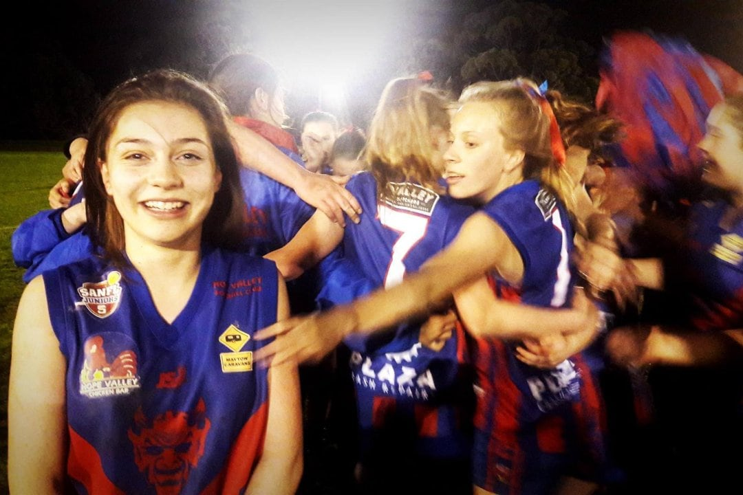 A group of girls in club Australian Rules Football uniforms are in a team huddle. A dark haired girl is standing in front of the huddle smiling at the camera and a blonde haired girl in the huddle is reaching towards the dark haired girl to pull her into the huddle.