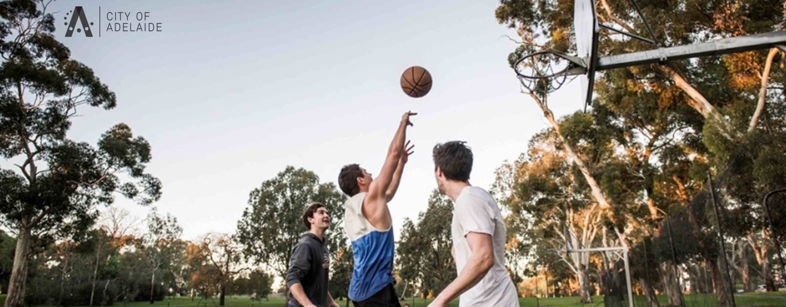 3 young men playing basketball in a park. City of Adelaide Council logo in top left corner of graphic
