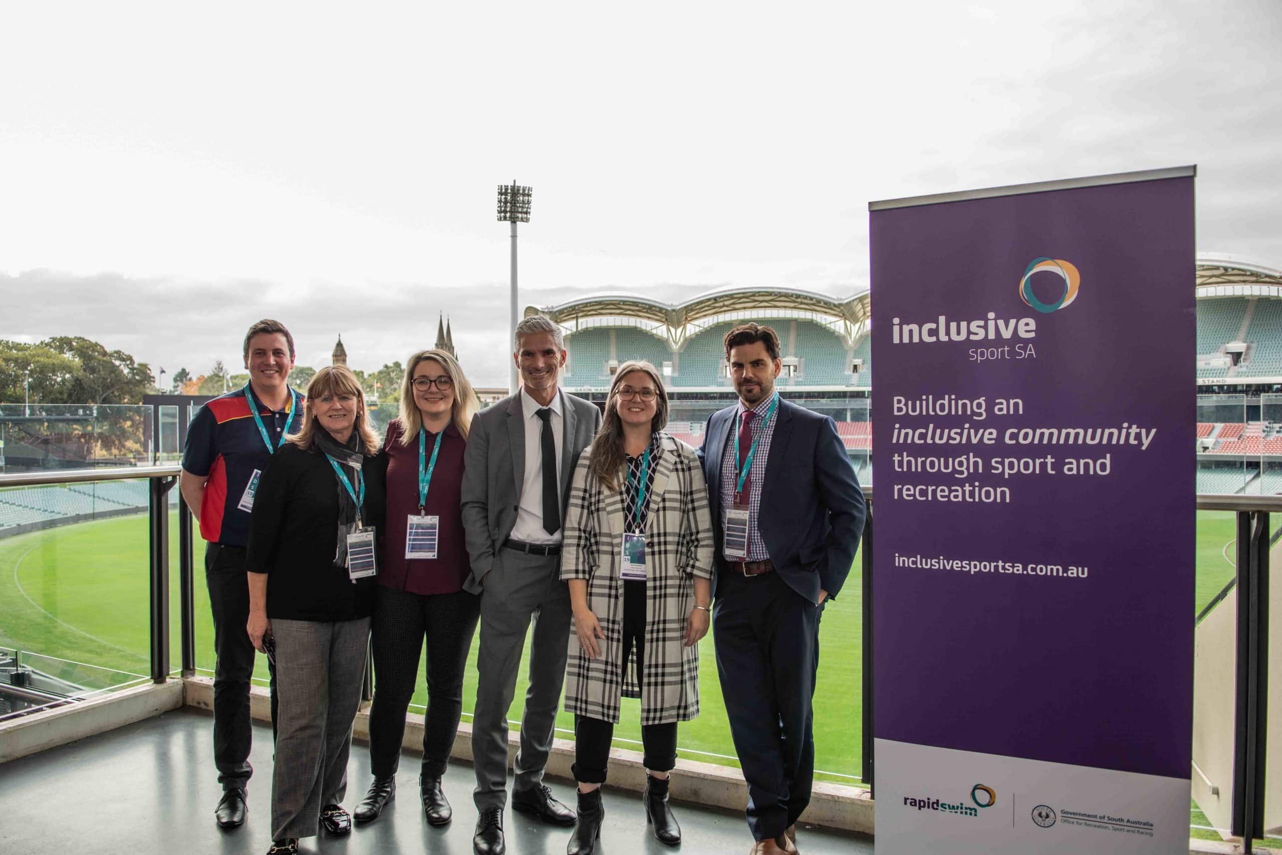 Group of six Active inclusion staff and collaborators standing on balcony with Adelaide Oval in the background.