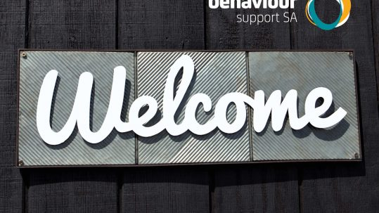 Image shows a sign featuring white text that says welcome on a tin background hung on a wooden wall. Behaviour Support SA logo is in top right corner of image.