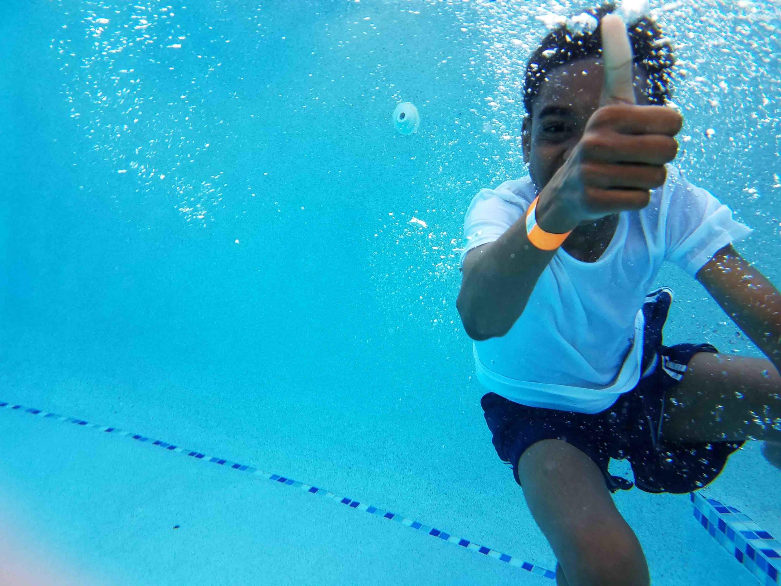 Young boy underwater gives a thumbs up