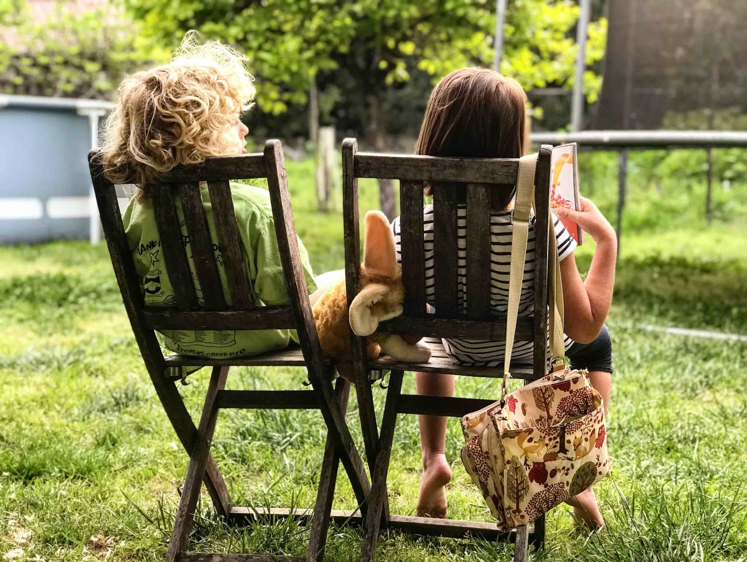 Two children sit on chairs next to each other in the garden. The young boy is talking to the young girl who is reading a book.