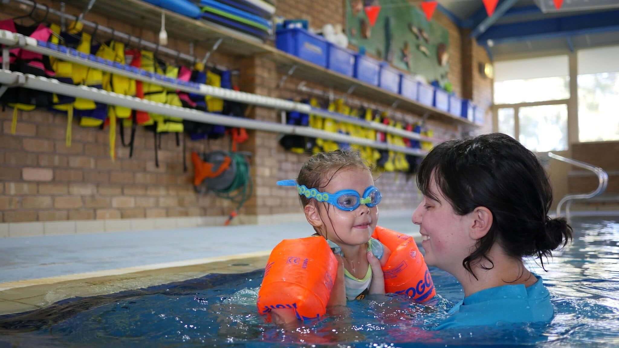 Female swimming teacher working with a young girl in a swimming pool during a lesson.