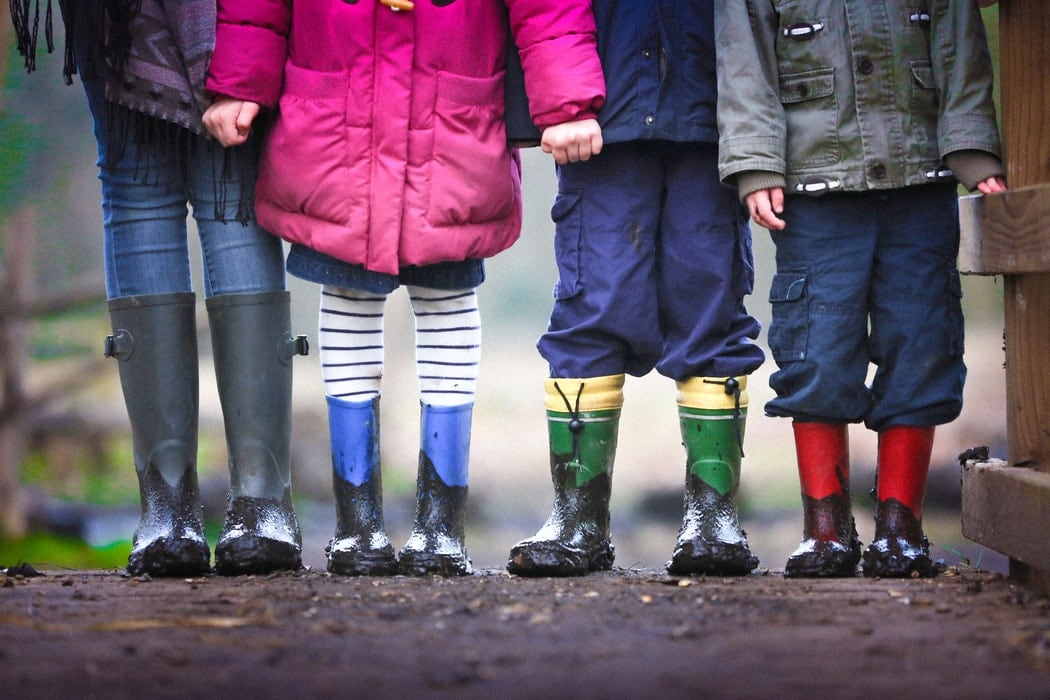 A group of four children are shown from the chest down standing on a wet path outsidewearing winter clothes and gum boots.