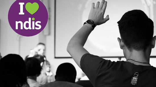 Man at the front of a room of people points to a man who has his hand up to ask a question. The I love NDIS logo appears in the top left corner.