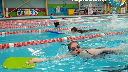 A female child holding a green kickboard swims in a race in a pool. Rapidswim logo in top left corner.