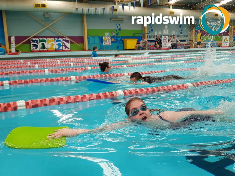 A female child holding a green kickboard swims in a race in a pool. Rapidswim logo in top left corner.