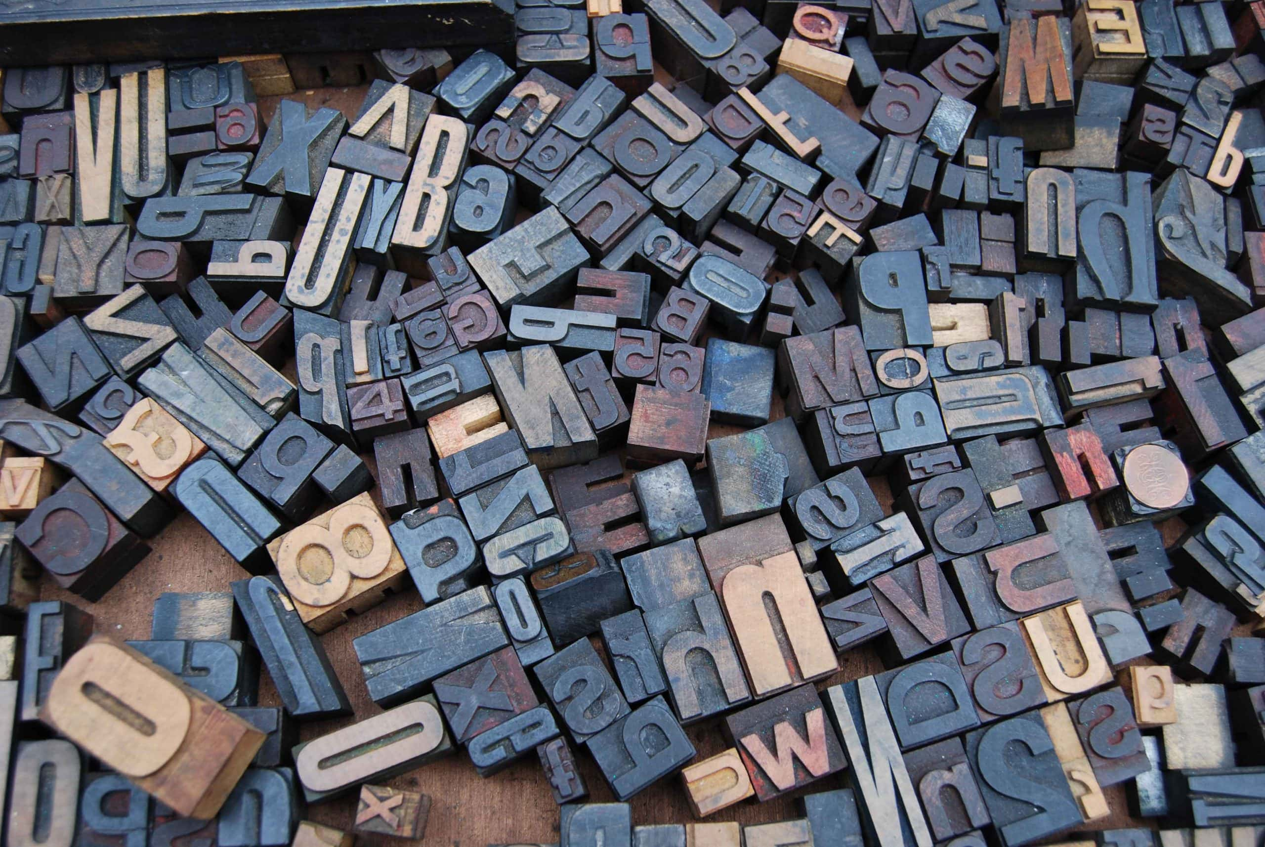 Image of a pile of letter and number stamps. They form no words, just randomly placed.
