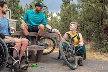A young man using a wheelchair sits by a picnic table outdoors, a another man sits on the table and is passing a drink to a woman sitting on a handcycle bike. on a