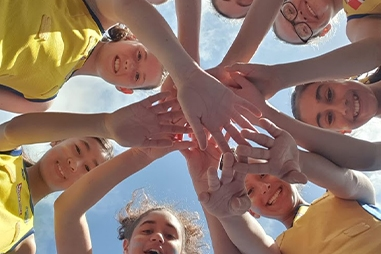 A group of young girls in sport uniforms look down at the camera. They have their hands in the middle on top of each other.