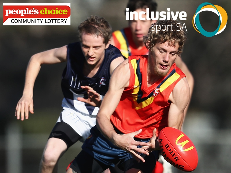 A South Australian State Football Player is running for the football a Victorian Player is close behind chasing him. Inclusive Sport SA logo and People's Choice Credit Union Community Lottery logos appear at top of image