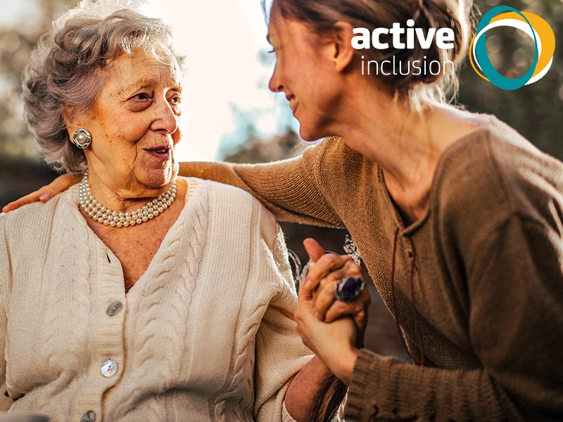 An older woman sits outside smiling. She is talking to a younger woman who has her arm around her and is holding her hand. The Active Inclusion logo is in the top right corner.
