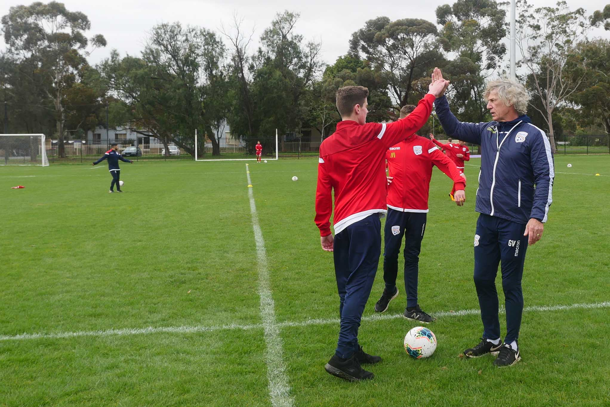 Image of a young man high giving a soccer coach of the pitch.