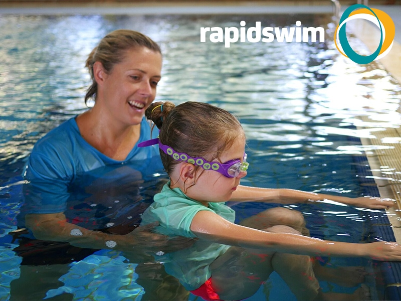 Image of a younger girl in a pool. A swimming instructor is teaching her to swim. The Rapidswim logo appears in the top right corner of the image.