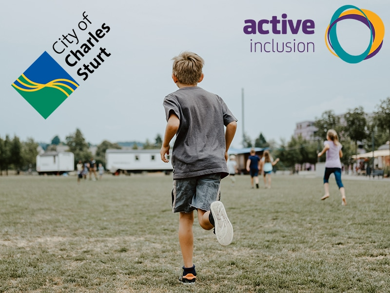 Image of a young boy running across grass in a outdoor park area away from camera. In the background other children are also running. The City of Charles Sturt and Active Inclusion logos appear at the top of the image