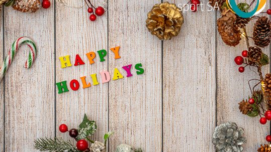 Image of christmas tree leaves, and candy canes on a wooden background. Multicolour letters spell Happy Holidays. The Inclusive Sport SA logo appears in the top right corner.