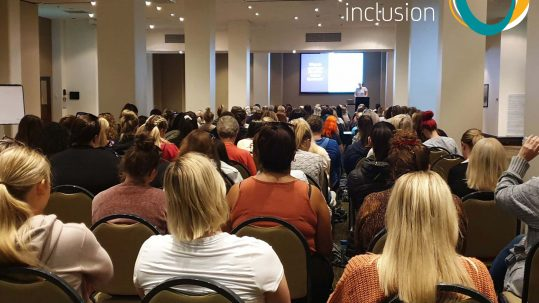 Image shows a room full of people at a conference. At the front of the room is a screen everyone is watching this and the person presenting. The Active Inclusion logo appears in the top right corner of the image.