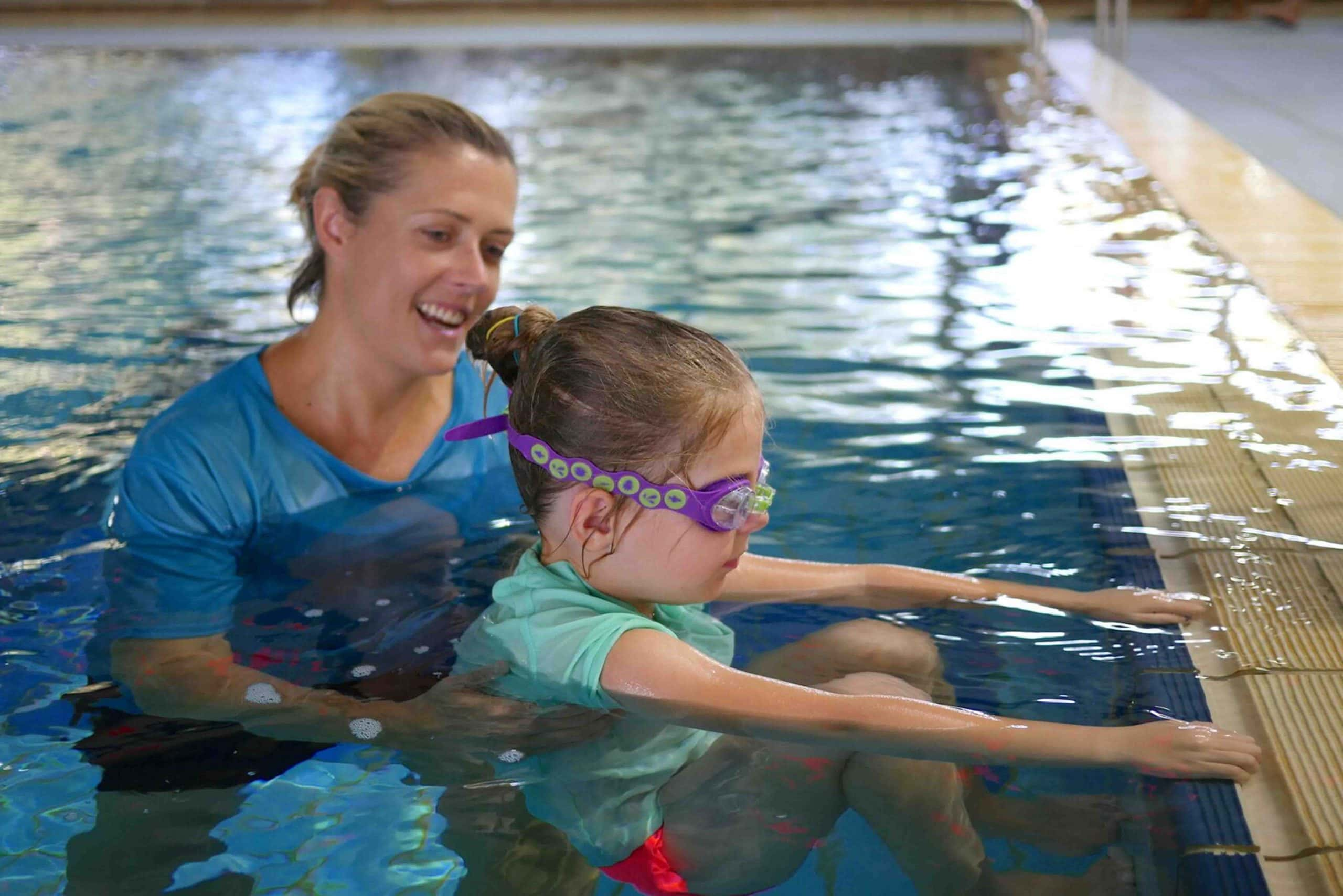 A female swimming instructor is teaching a young girl in a swimming pool.