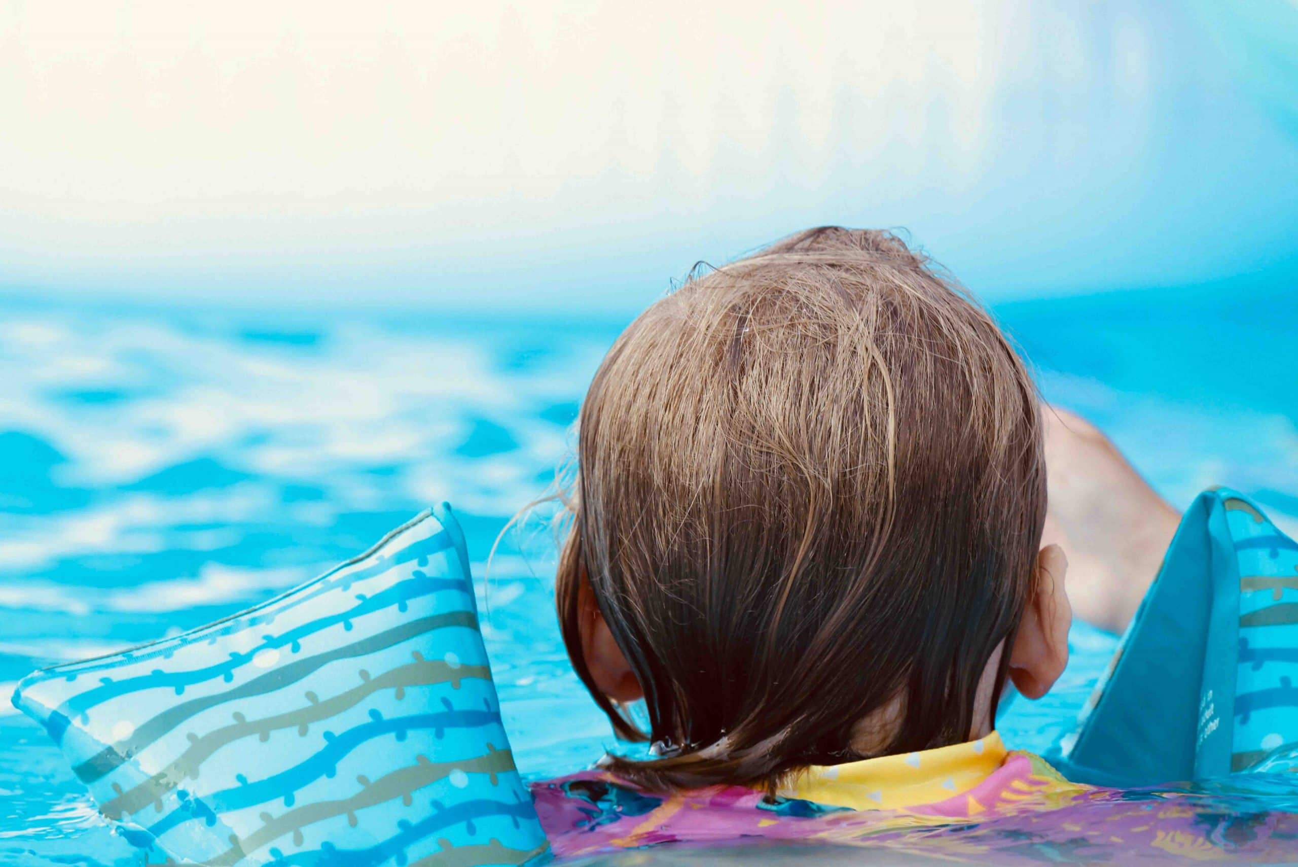 Image shows the back of a child's head and shoulders floating in a swimming pool with floaties on.
