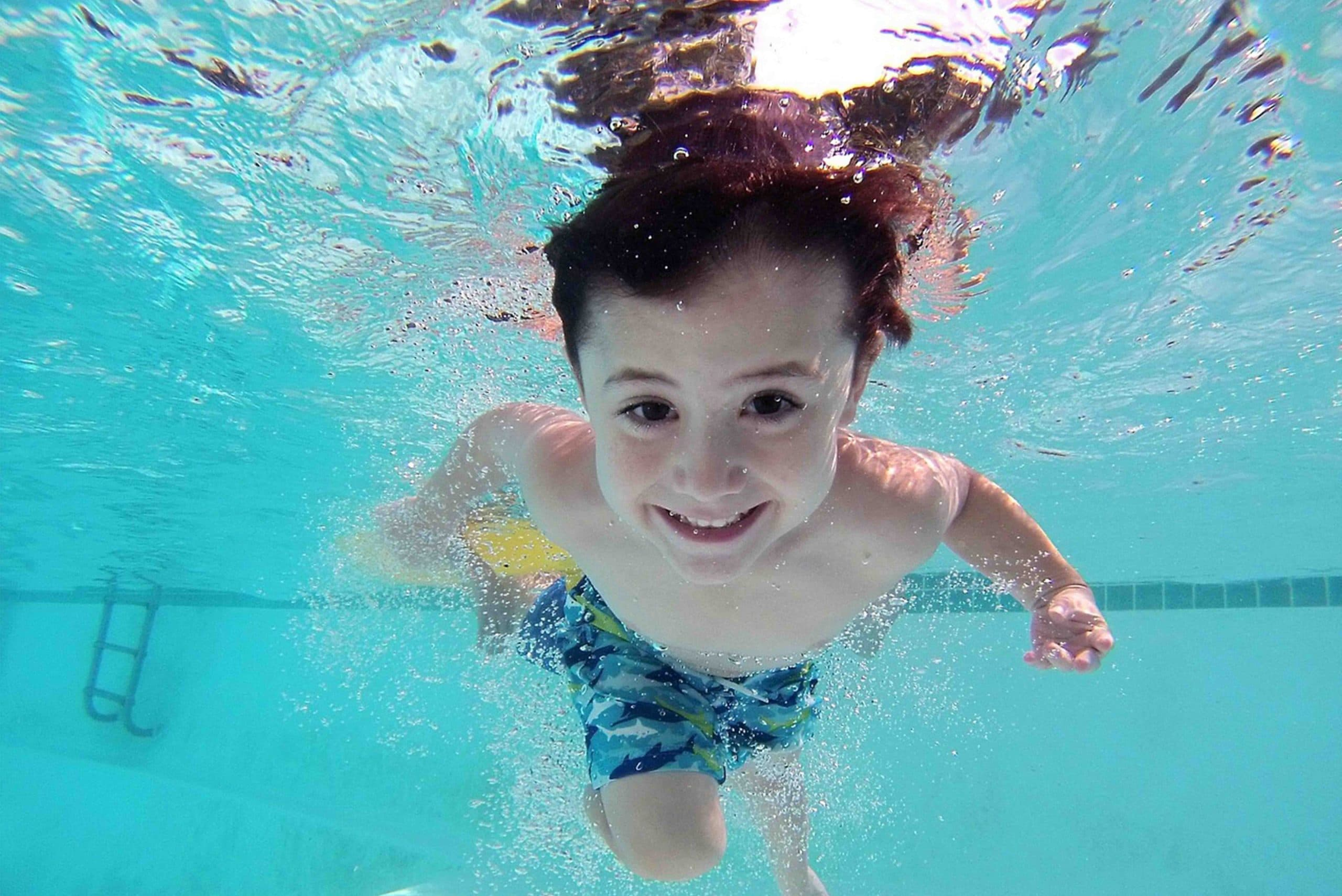 Young boy under water in a swimming pool he is smiling at the camera