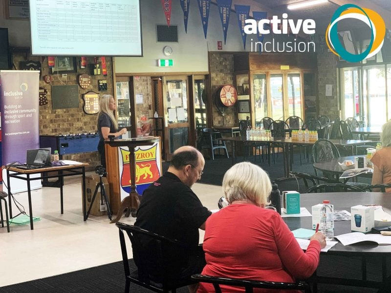 Image shows Active Inclusion General Manager Katrina Ranford at a podium in a sport club rooms talking to a group of people sitting at tables. The Active Inclusion logo appears in the top right hand corner.