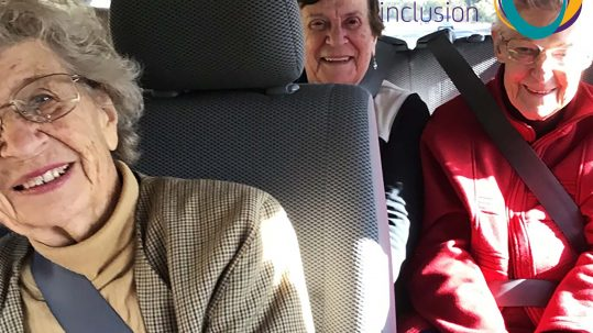 Image of three older women in a mini bus smiling at the camera. The Active Inclusion logo appears in the top right corner.