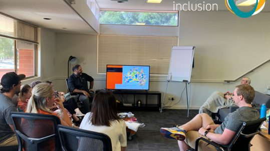 Image of office staff listening as Haydyn from Bookabee presents session on Aboriginal Cultural Sensitivity and Respect Training. The Active Inclusion logo appears in the top right hand corner.