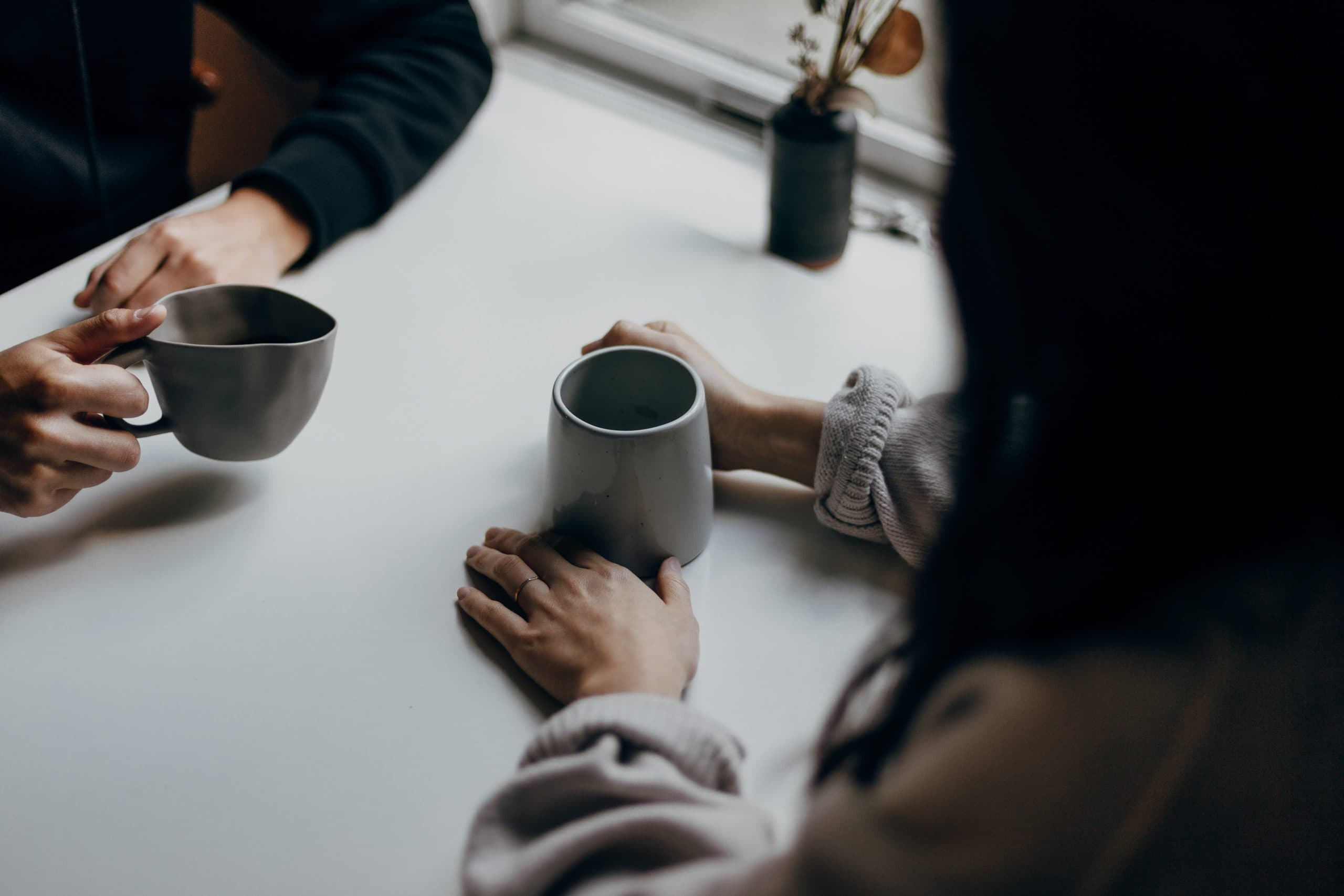 Image of two women's hands. They are both holding coffee mugs and are sat at a table facing each other.