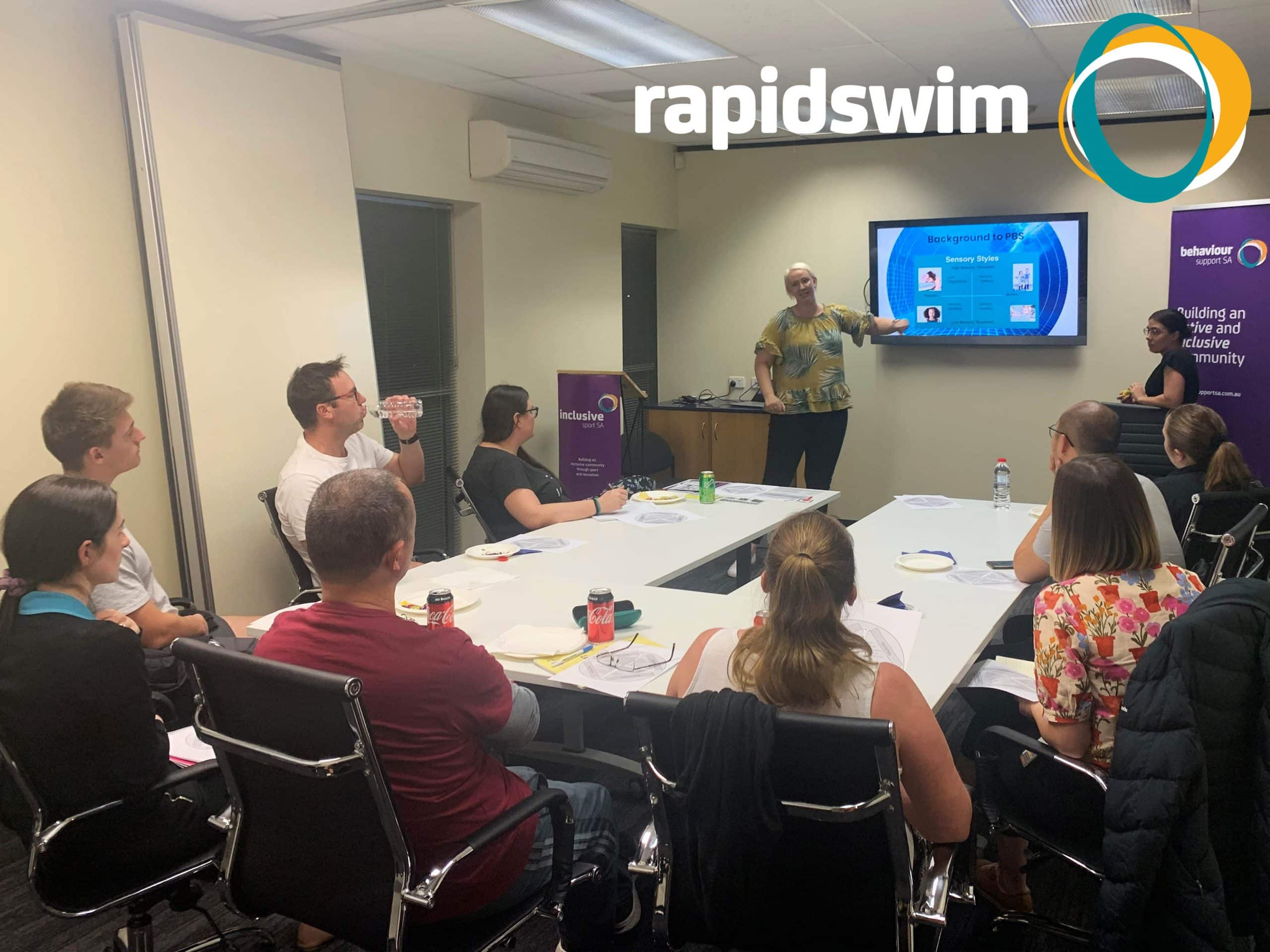 BSSA Practitioner Tamsin Petzer and Clinical Lead Bianca Dubois are giving a presentation a room of Rapidswim staff sit at a board room table listening. The Rapidswim logo appears in the top right hand corner.