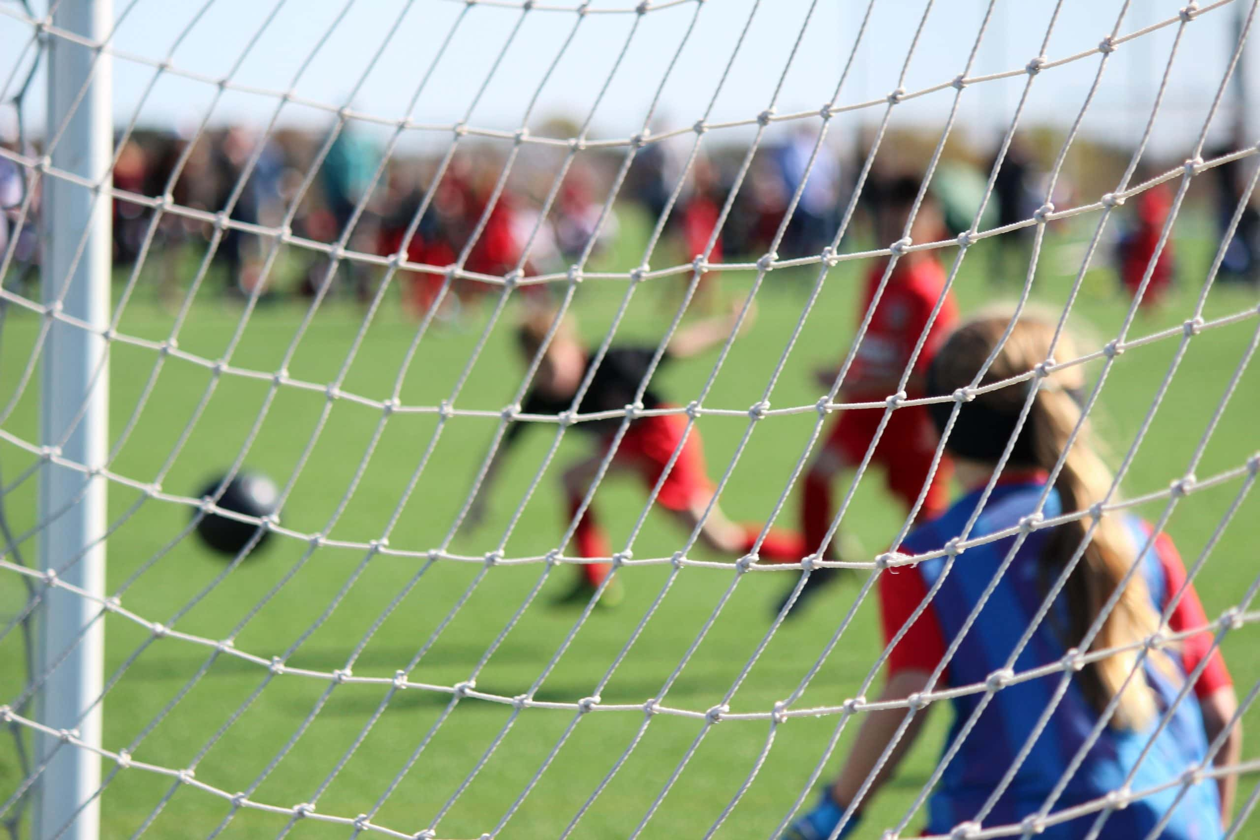 Image from behind a football goal net. In the distance a child is kick a ball towards the child in the goals.