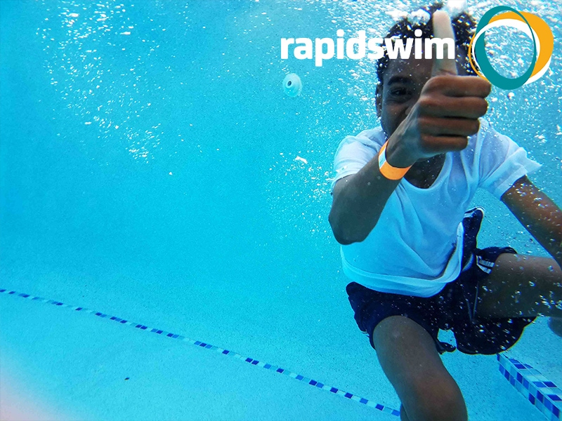 A young boy is underwater smiling and giving a thumbs up gesture. The Rapidswim logo appears in the top right hand corner.